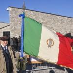 Il comm. Lino Felician con la bandiera dell'ANMIG di Trieste a Basovizza sferzata dalla bora